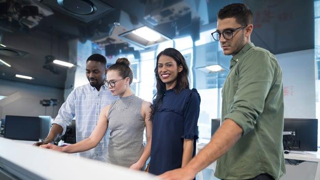 Cuatro compañeros de trabajo interactuando con pantalla táctil inteligente