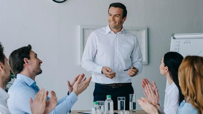 Un empresario en mesa de trabajo motivando a sus empleados